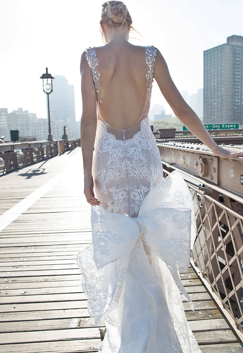 A Pnina Tornai lace mermaid fit and flare wedding dress with a low back and a bow
