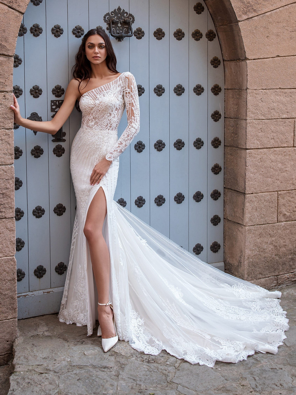 A Pronovias long sleeve, one shoulder mermaid wedding dress, with lace and detailed embellishments