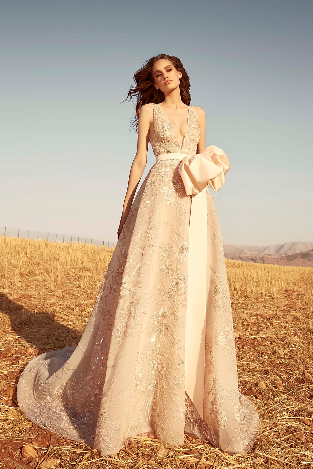 A Zuhair Murad blush A-line wedding dress with beading and a bow