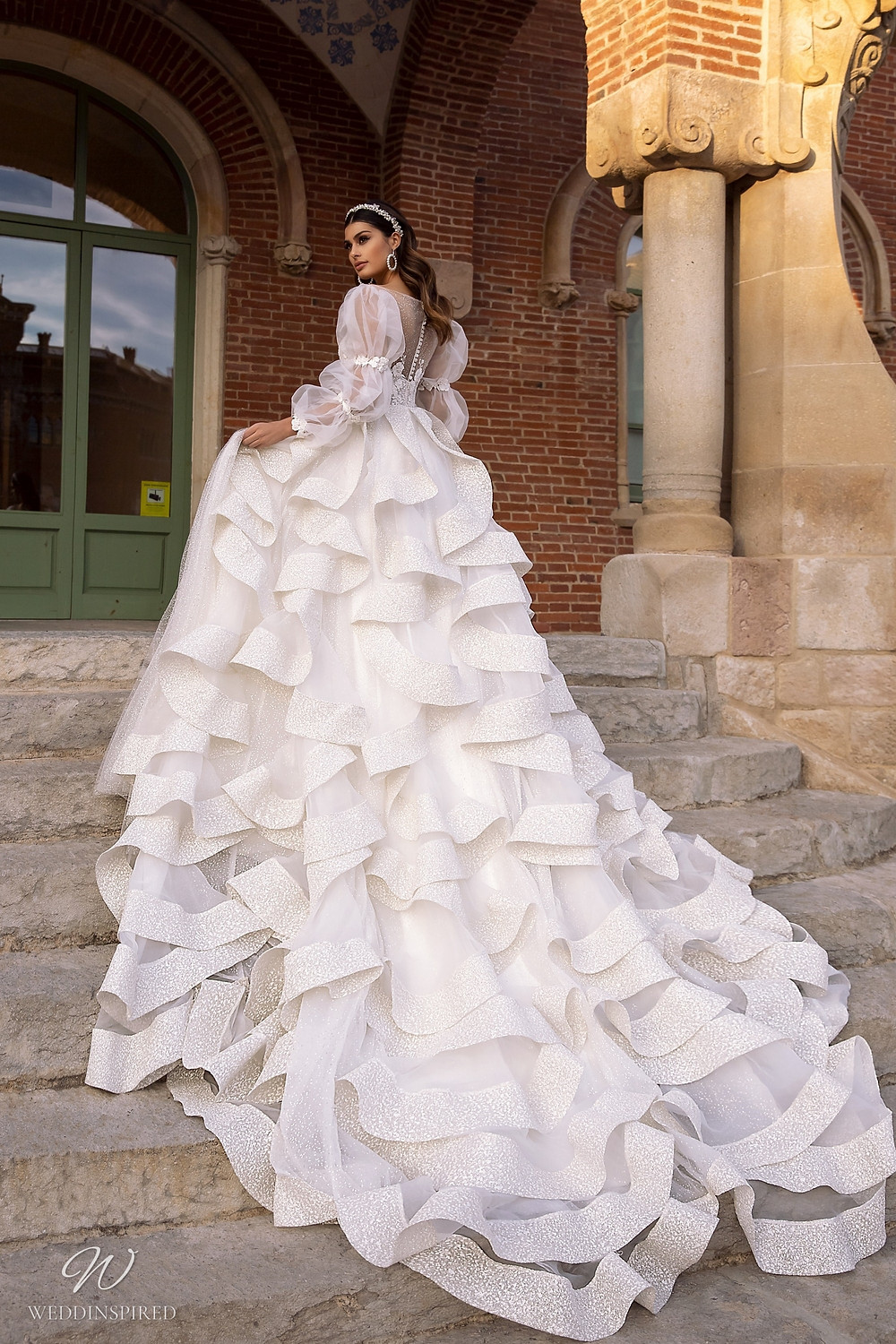 A Maks Mariano princess ball gown wedding dress with layered ruffle skirt and long tulle sleeves