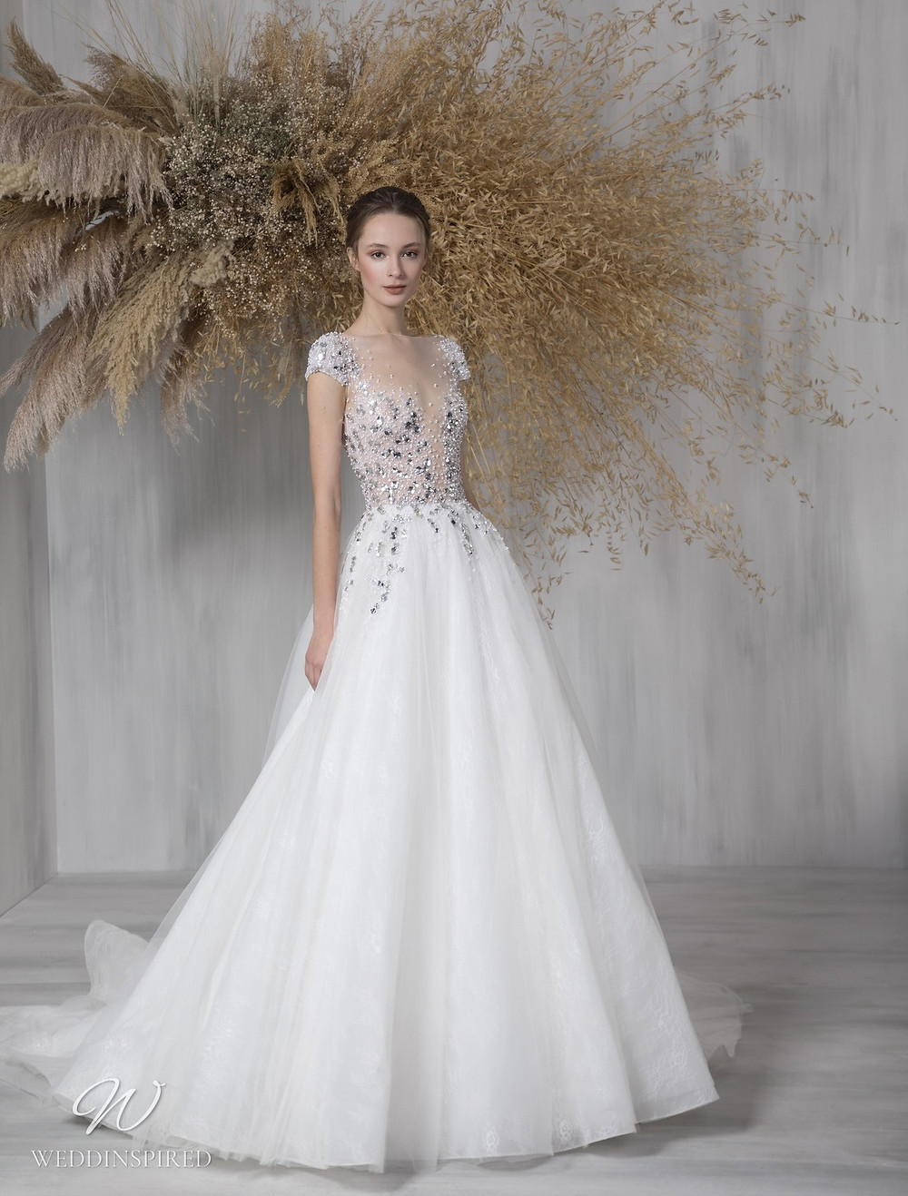 A Tony Ward 2021 sparkly tulle Cinderella princess ball gown wedding dress with cap sleeves and an illusion neckline