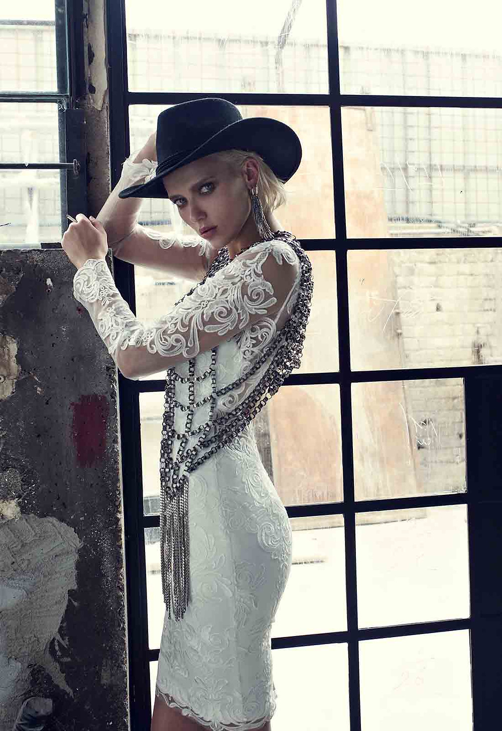 A Pnina Tornai short lace wedding dress with long illusion sleeves