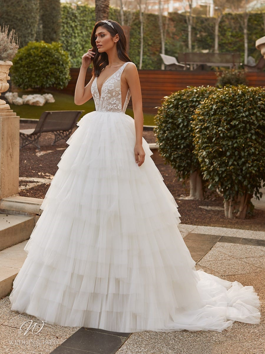 A Pronovias 2021 lace and mesh ball gown wedding dress with a ruffle skirt and a v neckline