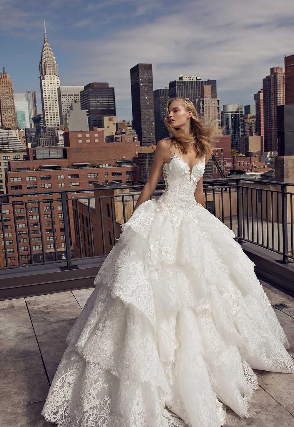 A Pnina Tornai lace princess ball gown wedding dress with a layered ruffle skirt