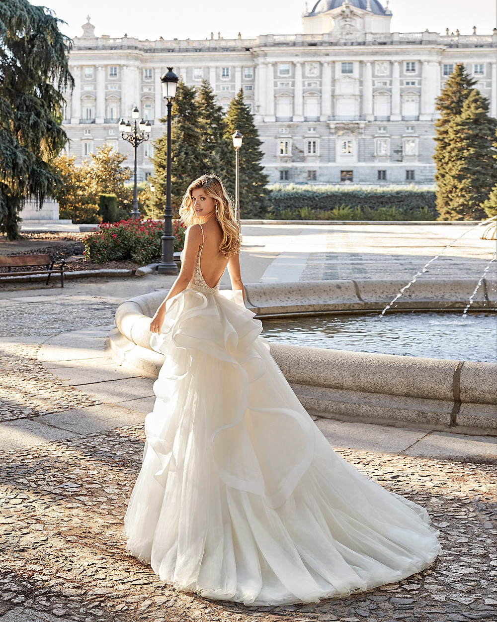An Aire Barcelona 2020 lace and tulle ball gown wedding dress with a layered ruffle skirt and a low back
