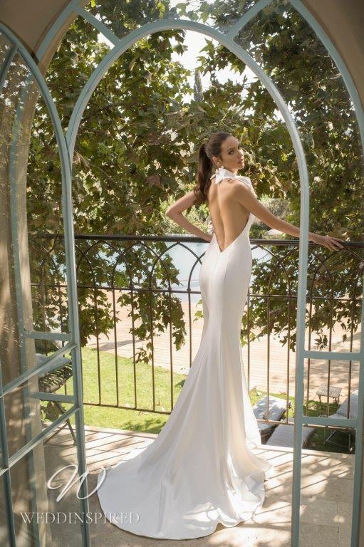 A David Hasbani satin halterneck mermaid wedding dress with a high neckline and a bow