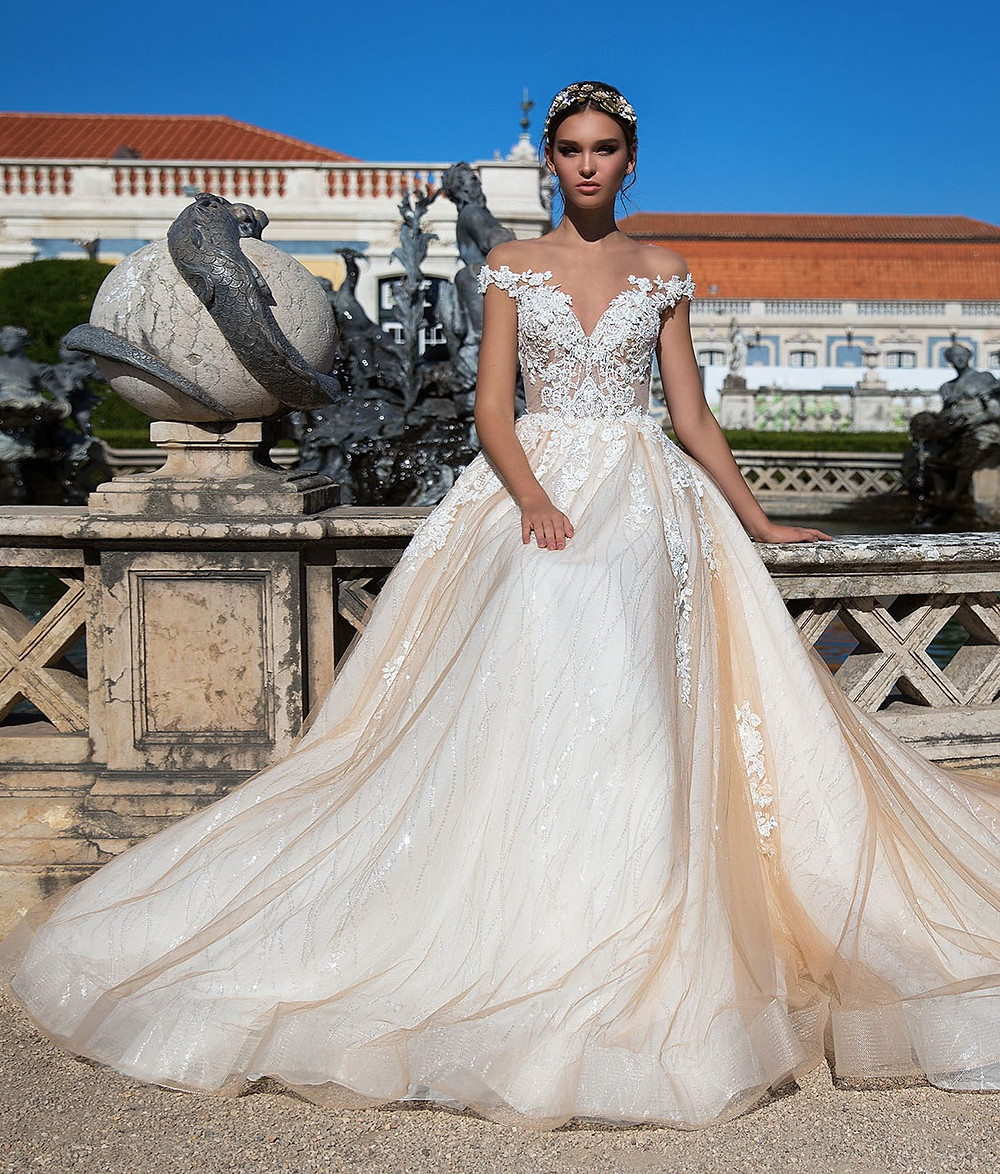 A Milla Nova off the shoulder blush peach lace ball gown wedding dress