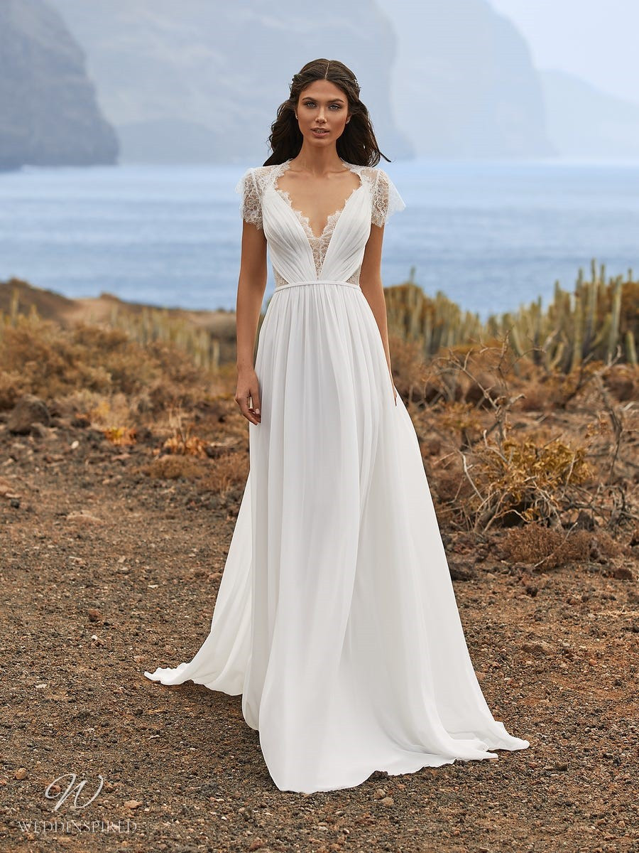 A Pronovias 2021 lace and chiffon Grecian style A-line wedding dress with cap sleeves