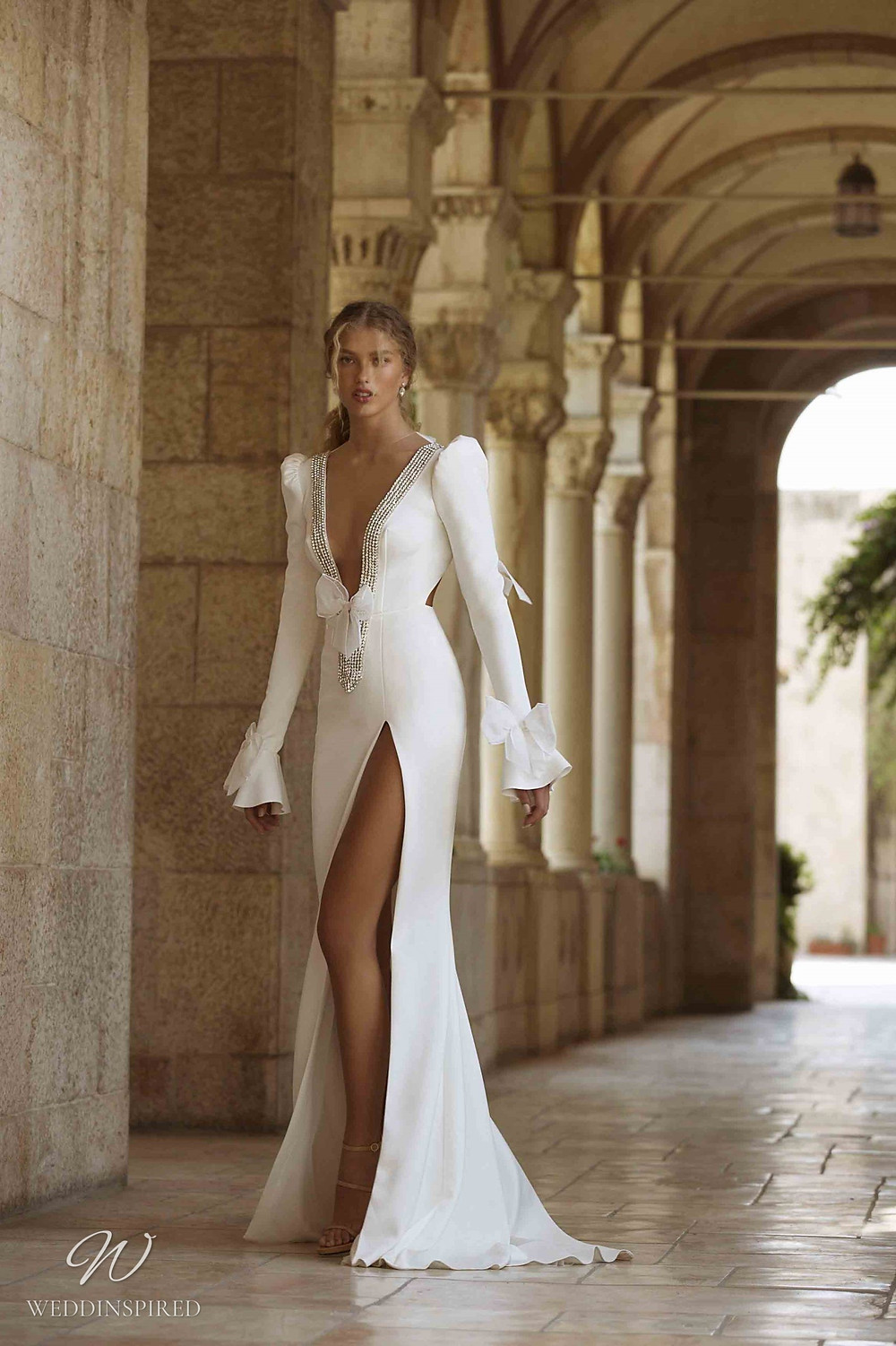A Berta Colony 2021 crepe fitted wedding dress with long puff sleeves, a high slit and a low v neckline