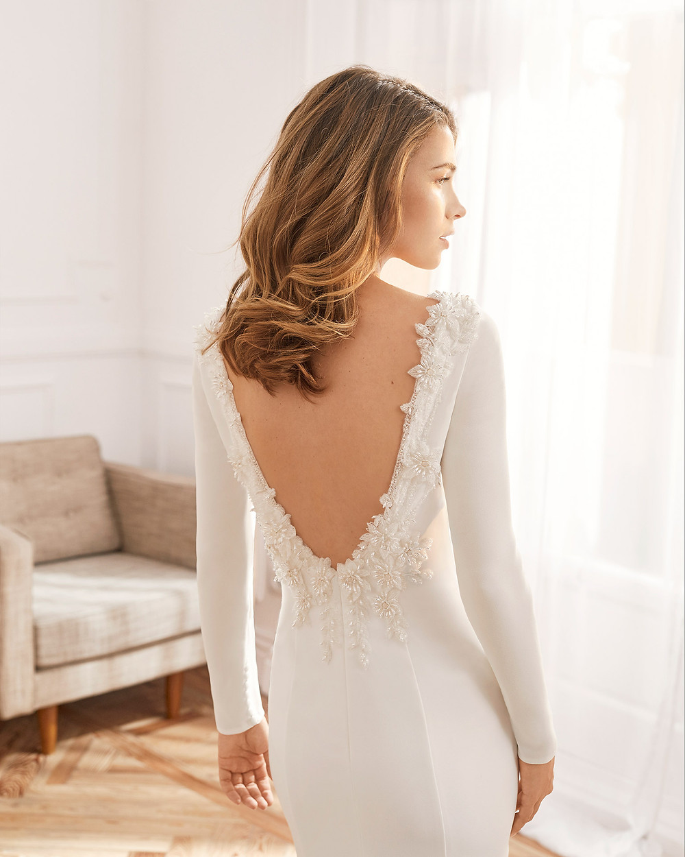 An Aire Barcelona 2020 crepe mermaid fit an flare wedding dress with long sleeves and a low back with beading