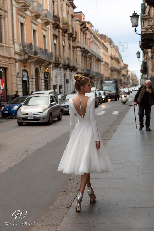 A Naviblue short tea length crepe wedding dress with long sleeves