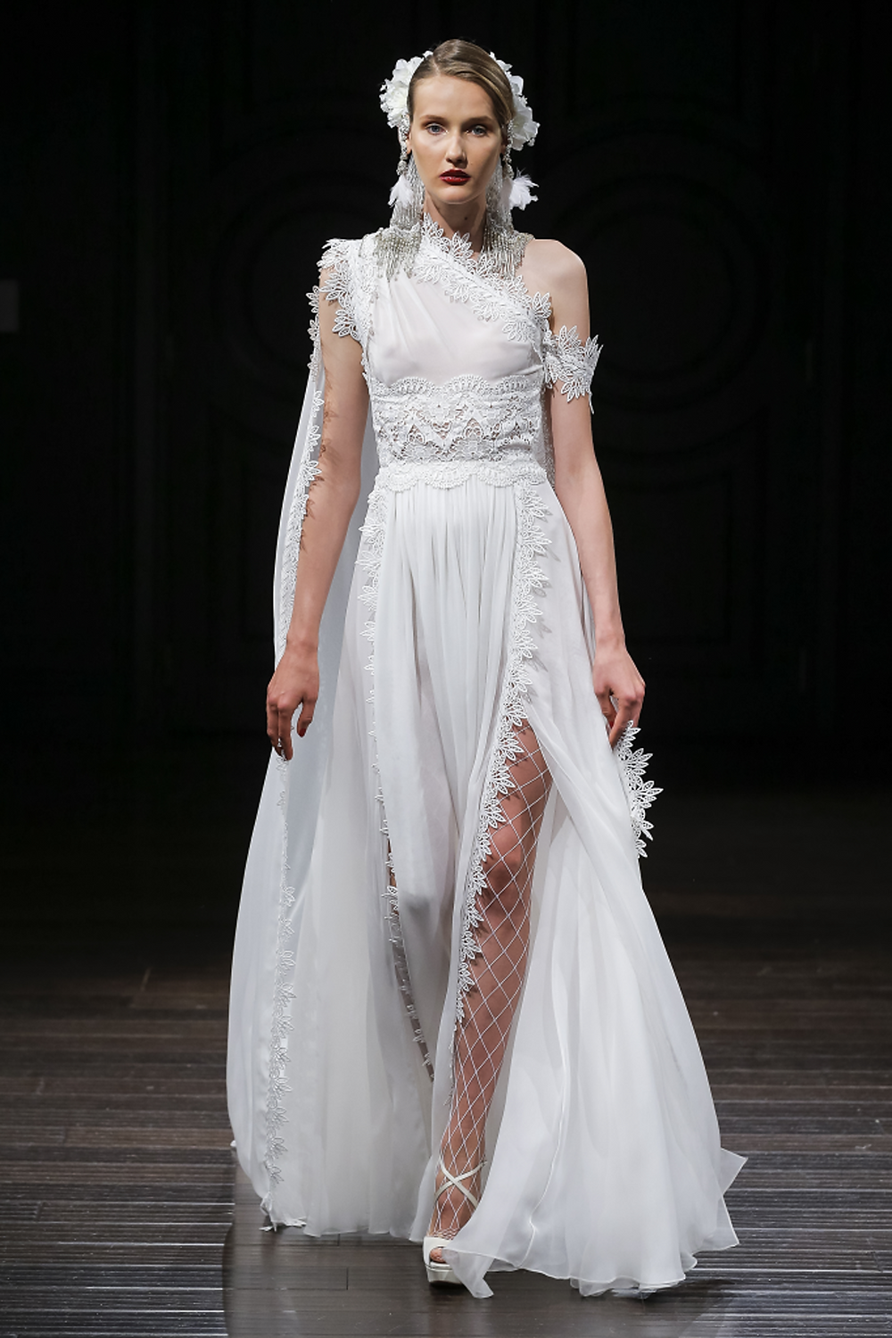 A detailed one shoulder, sheath wedding dress with floral embellishments