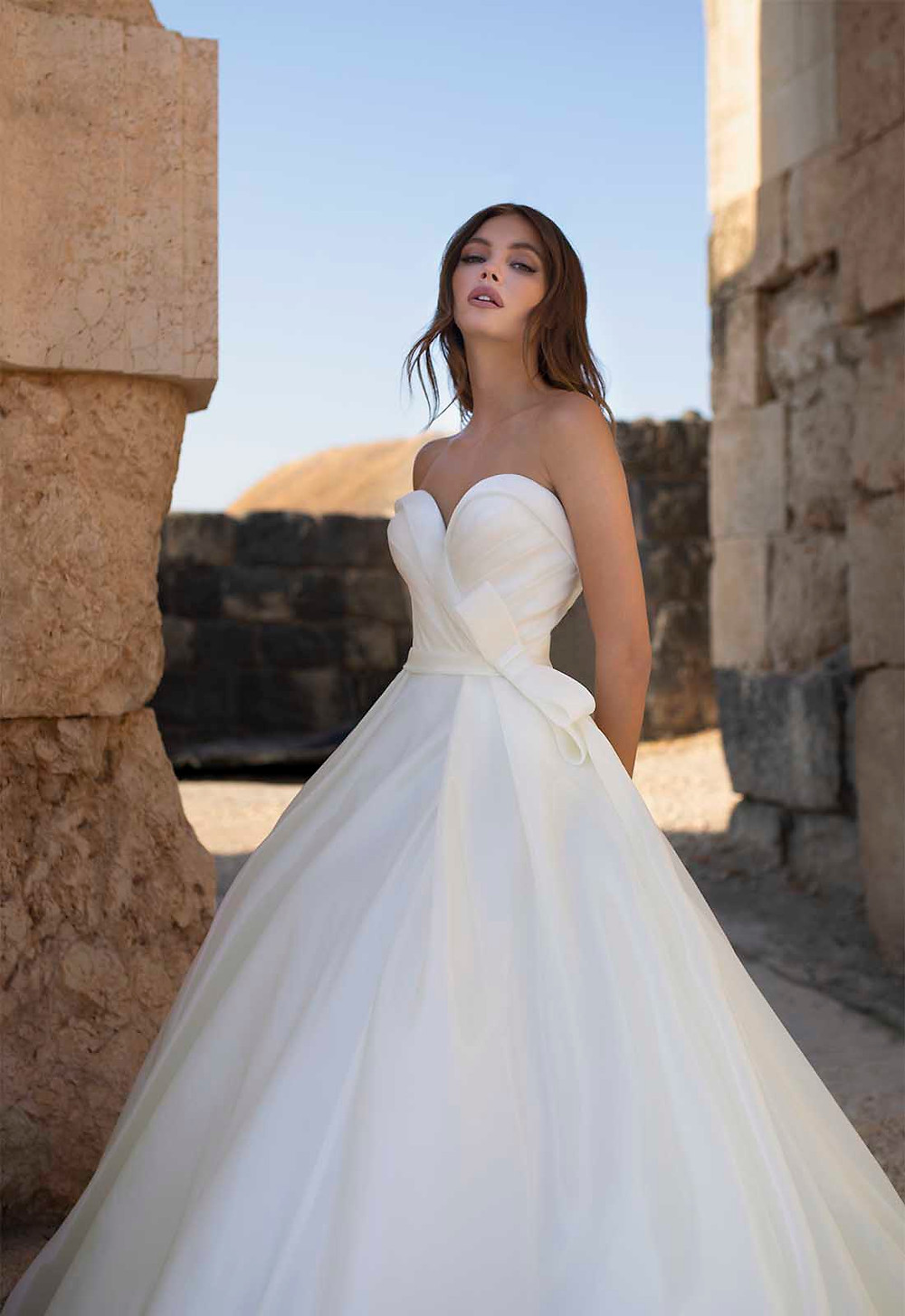 A Pnina Tornai strapless tulle ball gown wedding dress with a sweetheart neckline and a bow