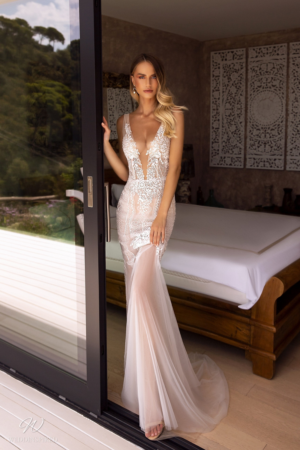A Tina Valerdi fit and flare tulle wedding dress with a deep v neckline