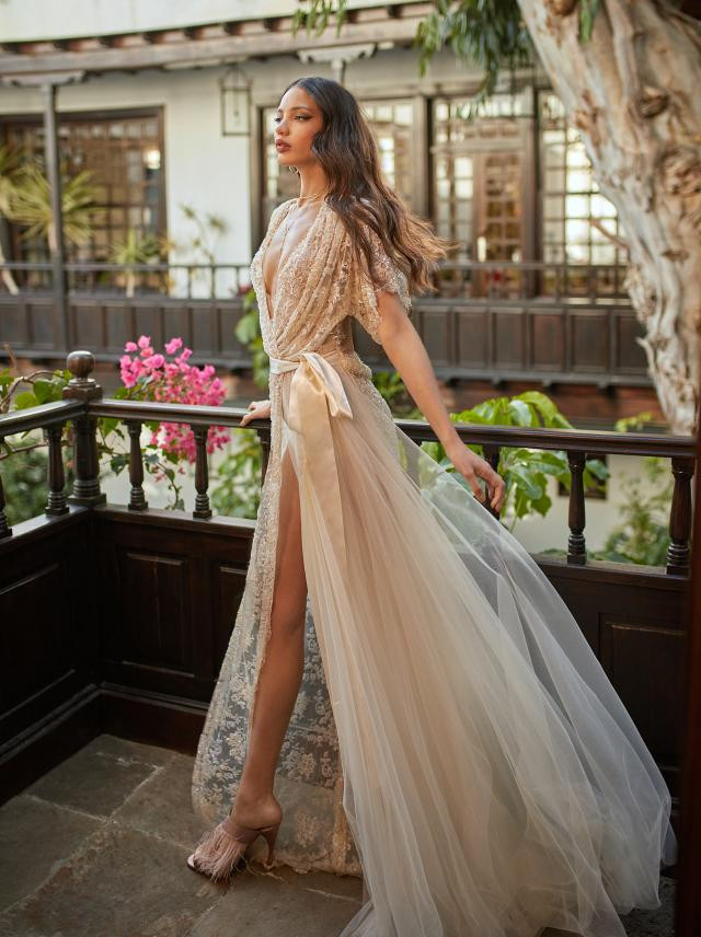 A tan A-line wedding dress, with tulle skirt, lace top and low v neckline