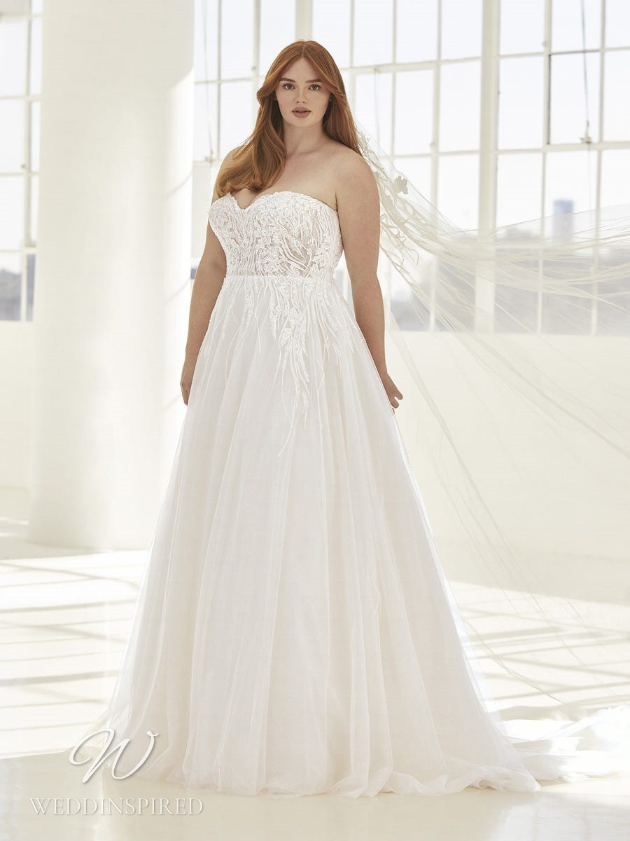 An Ashley Graham x Pronovias 2021 plus size strapless lace and tulle ball gown wedding dress