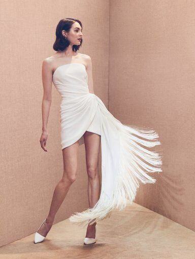 An Oscar de la Renta strapless short wedding dress with a fringe skirt