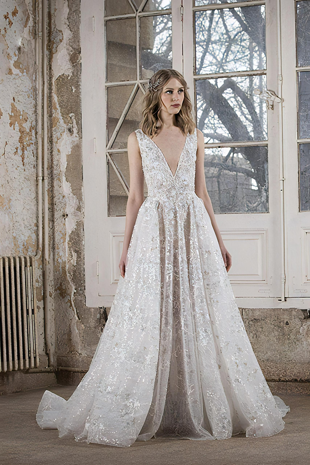 A deep-V wedding gown in embroidered lace accentuated with an illusion of an overskirt with large frills