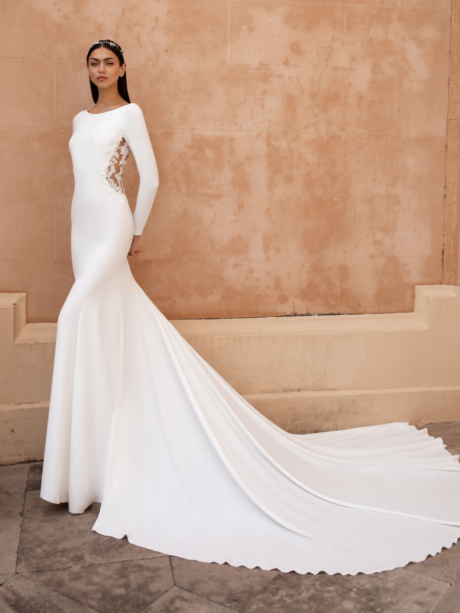 A Pronovias simple mermaid wedding dress with lace inserts and long sleeves
