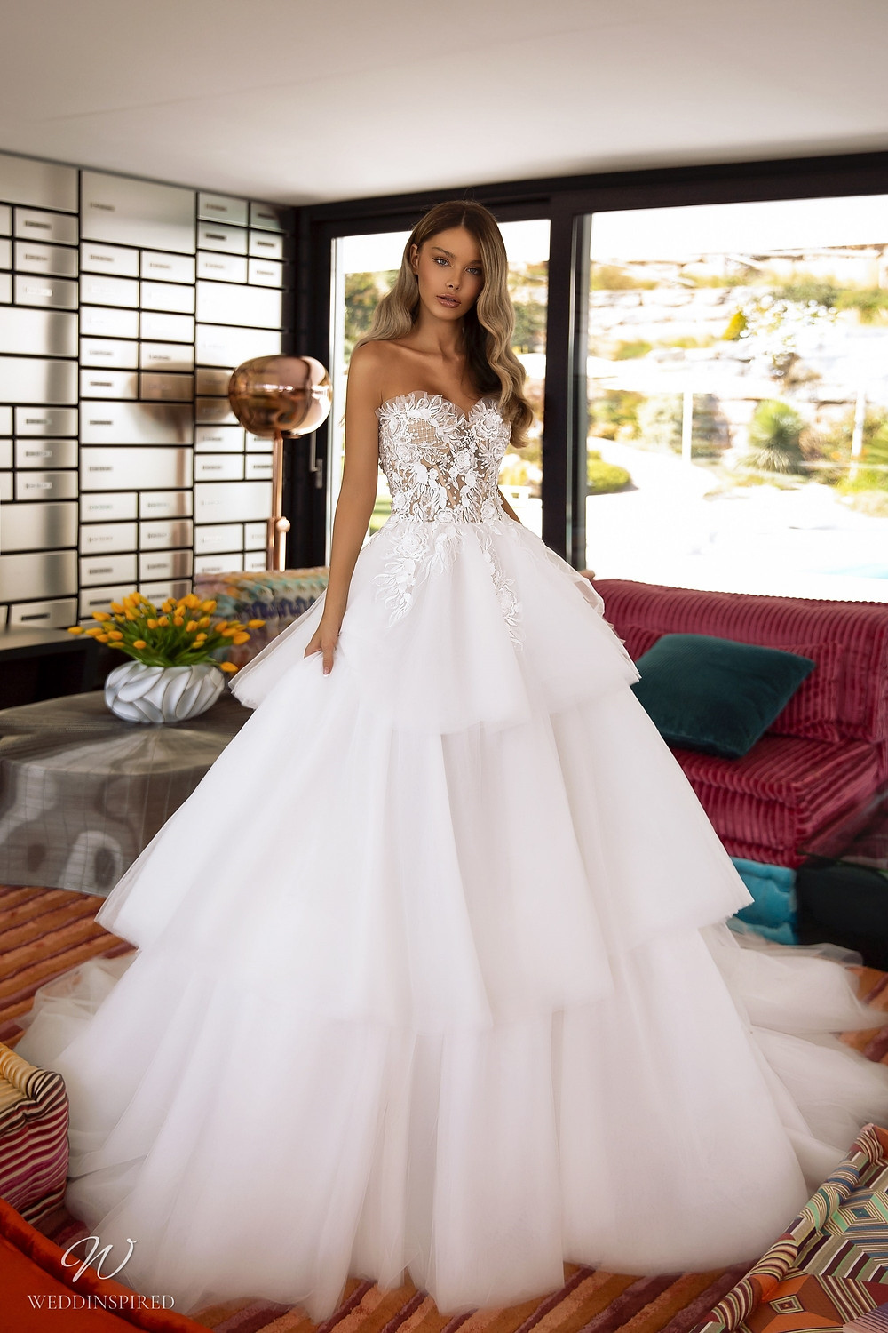 A Tina Valerdi strapless lace and tulle ball gown wedding dress with a layered ruffle skirt and a sweetheart neckline