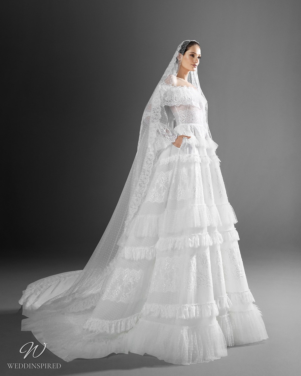 A Zuhair Murad off the shoulder ball gown wedding dress with ruffles, bell sleeves and a veil