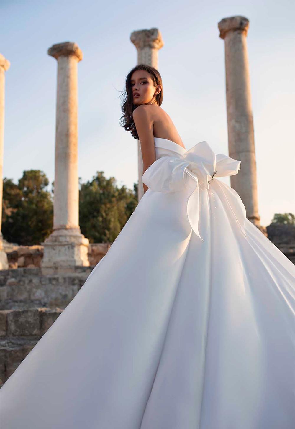 A Pnina Tornai strapless silk princess ball gown wedding dress with a bow