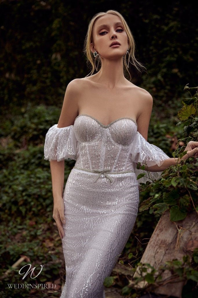 A Julie Vino 2021 off the shoulder sparkly mermaid wedding dress with a bustier top