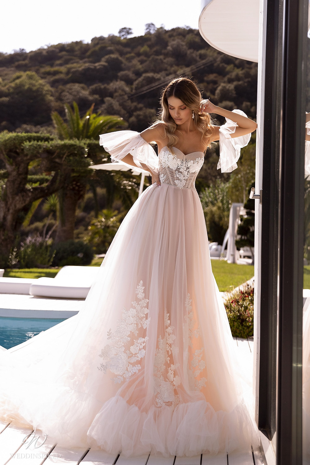 A Tina Valerdi strapless blush romantic ball gown wedding dress with tulle and lace