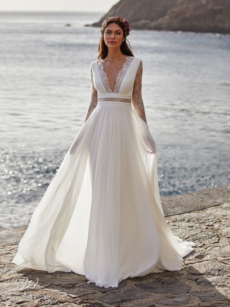 A Pronovias 2021 Grecian style lace and chiffon A-line wedding dress with long sleeves