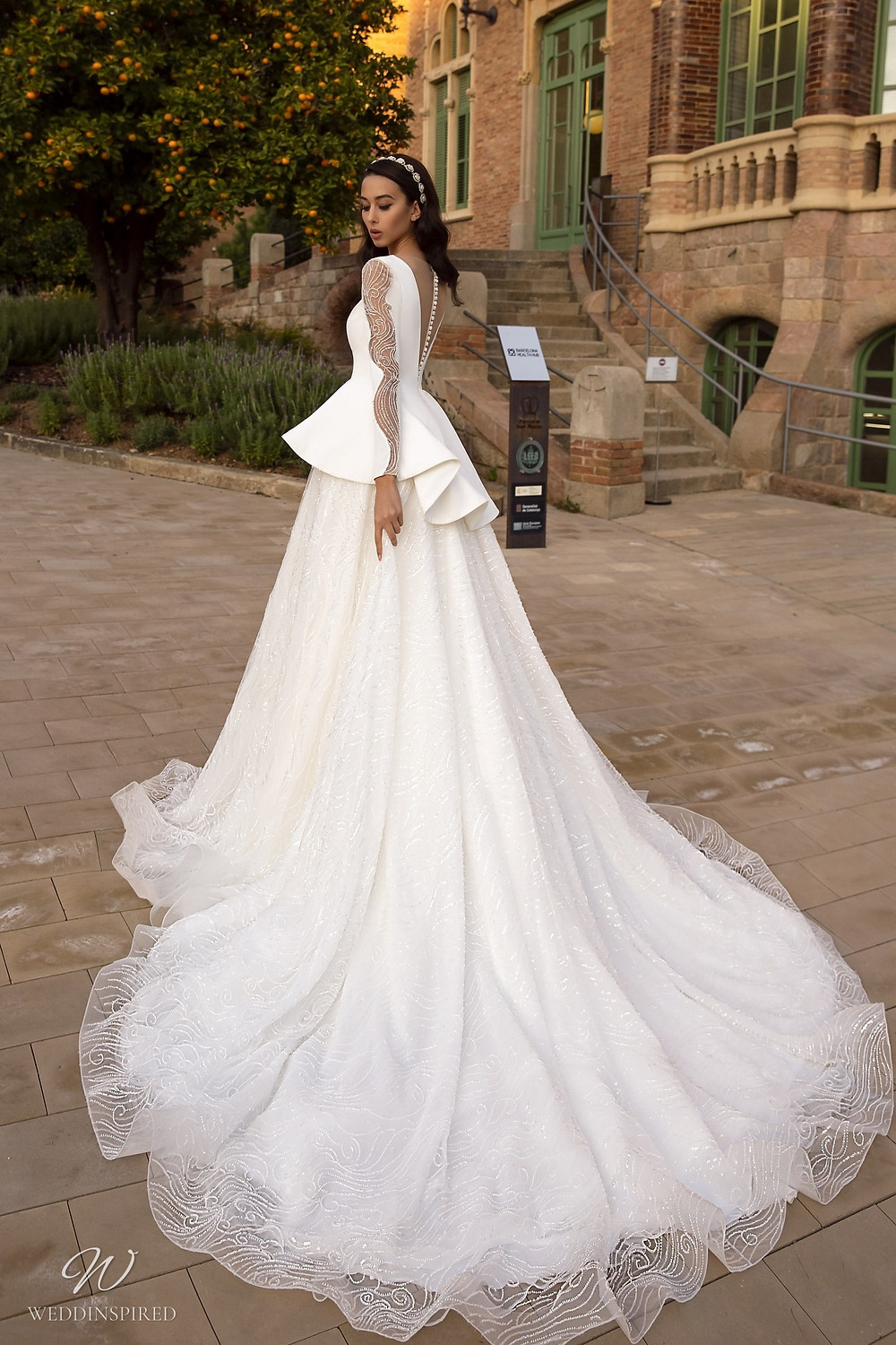 A Maks Mariano mesh princess ball gown wedding dress with long sleeves and a peplum