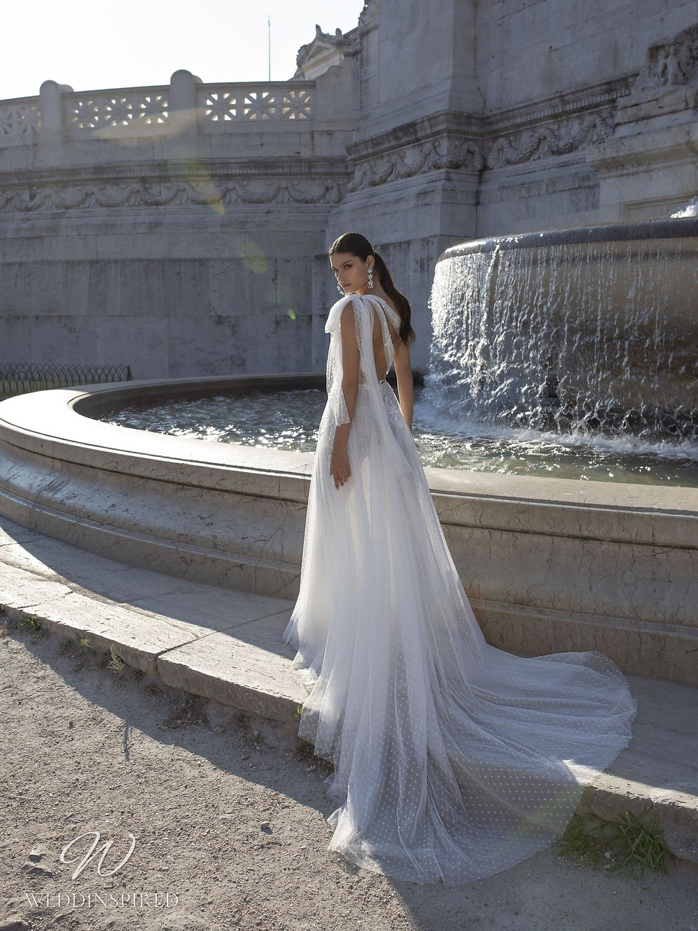 A Pinella Passaro one shoulder tulle A-line wedding dress with a bow