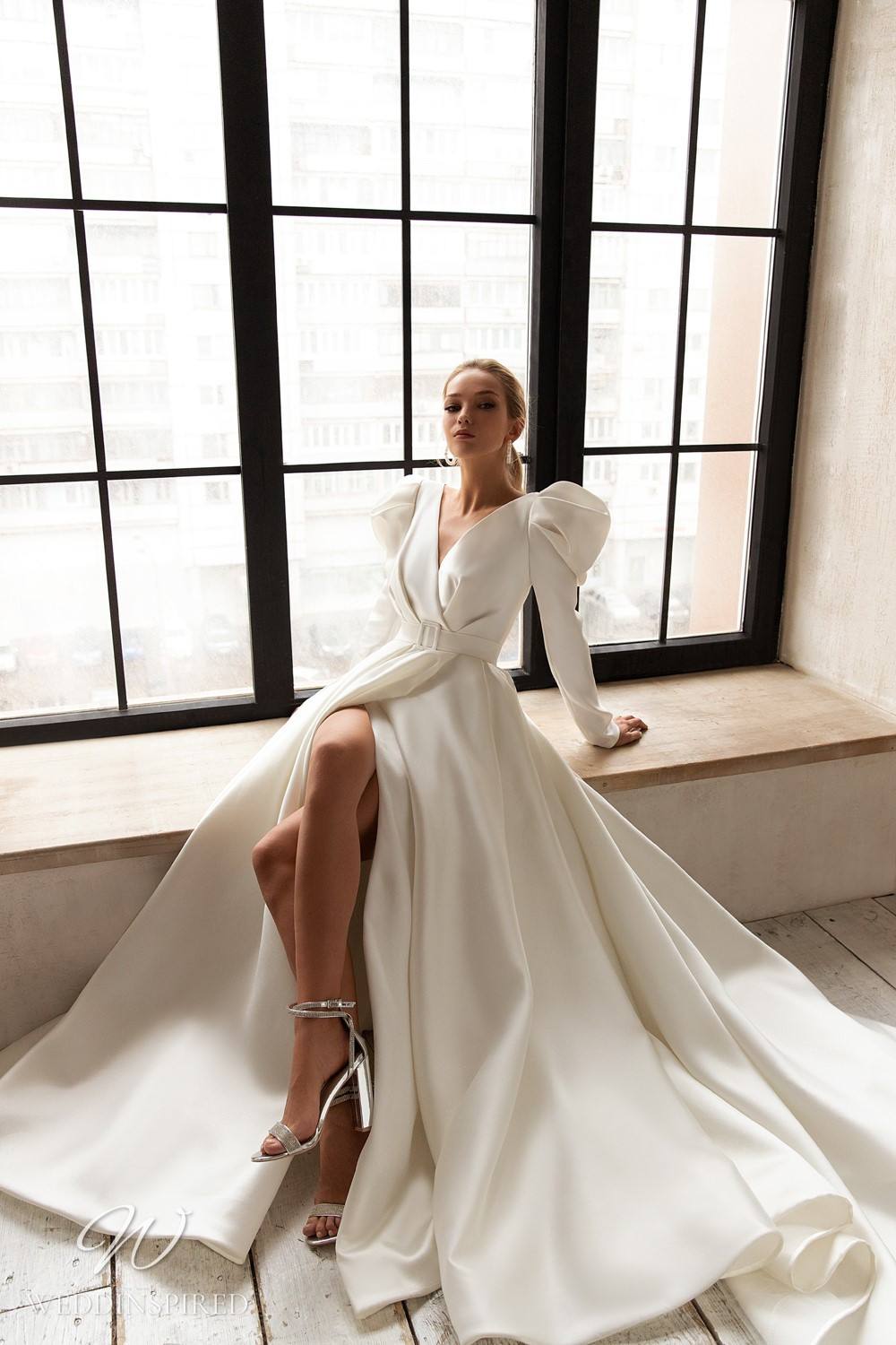 An Eva Lendel 2021 silk ball gown wedding dress with long puff sleeves and a high slit