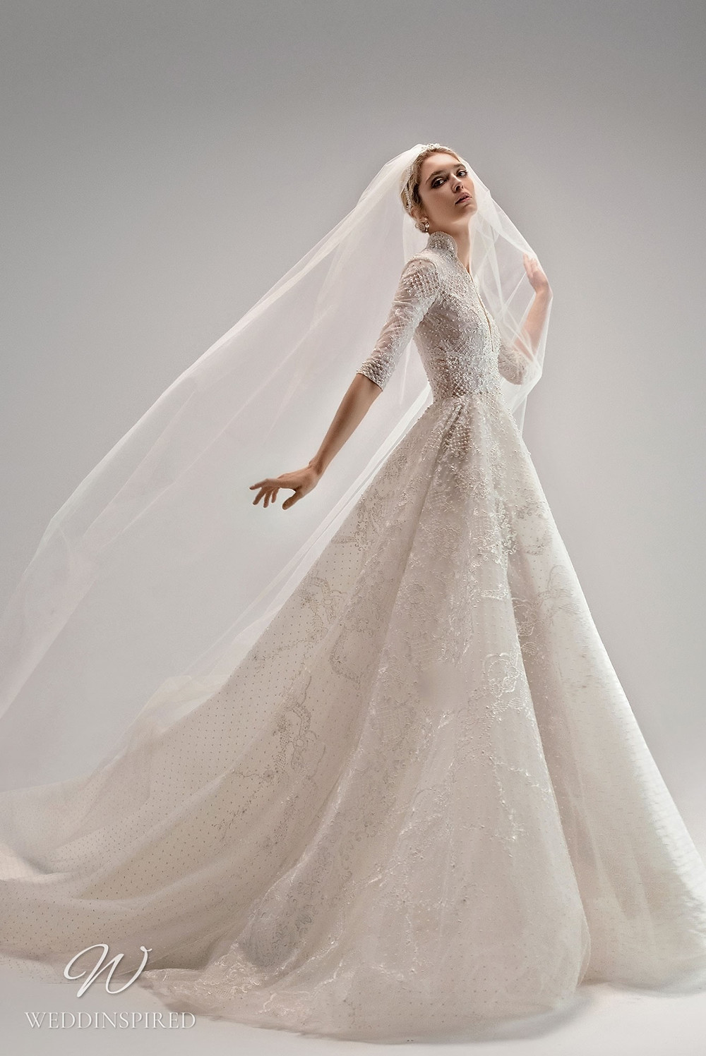 An Ersa Atelier 2021 tulle ball gown wedding dress with half sleeves, a high neck, beading and embroider