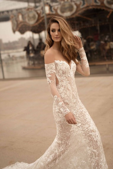 An off the shoulder, lace, sheath wedding dress with long sleeves