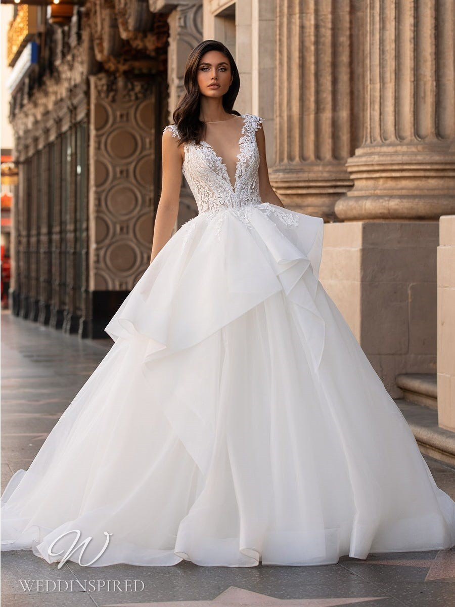A Pronovias 2021 lace and tulle princess ball gown wedding dress with cap sleeves and a ruffle skirt