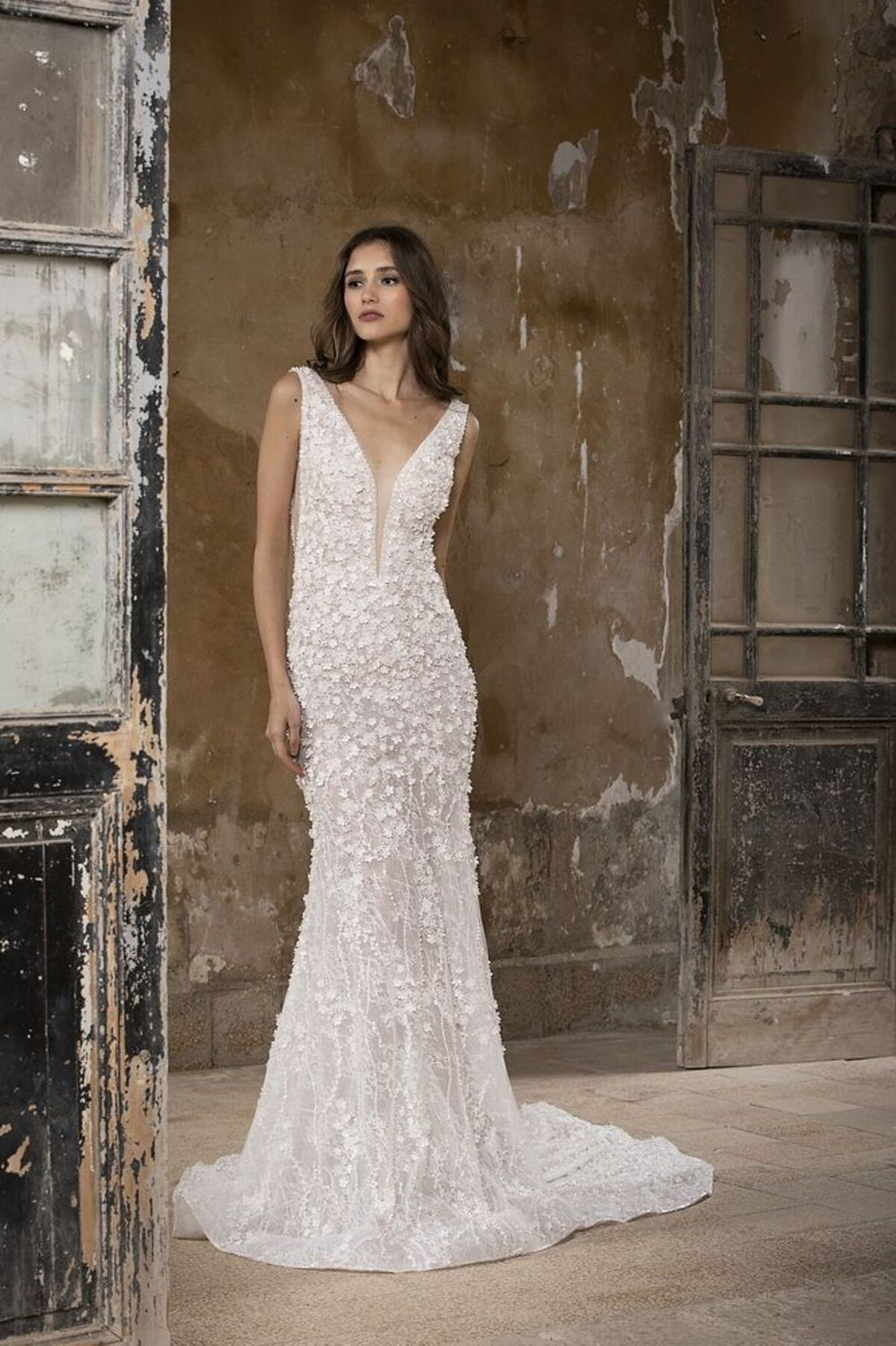 A mermaid-cut wedding gown with a deep-V, made with three-dimensional floral lace and scattered embroidery