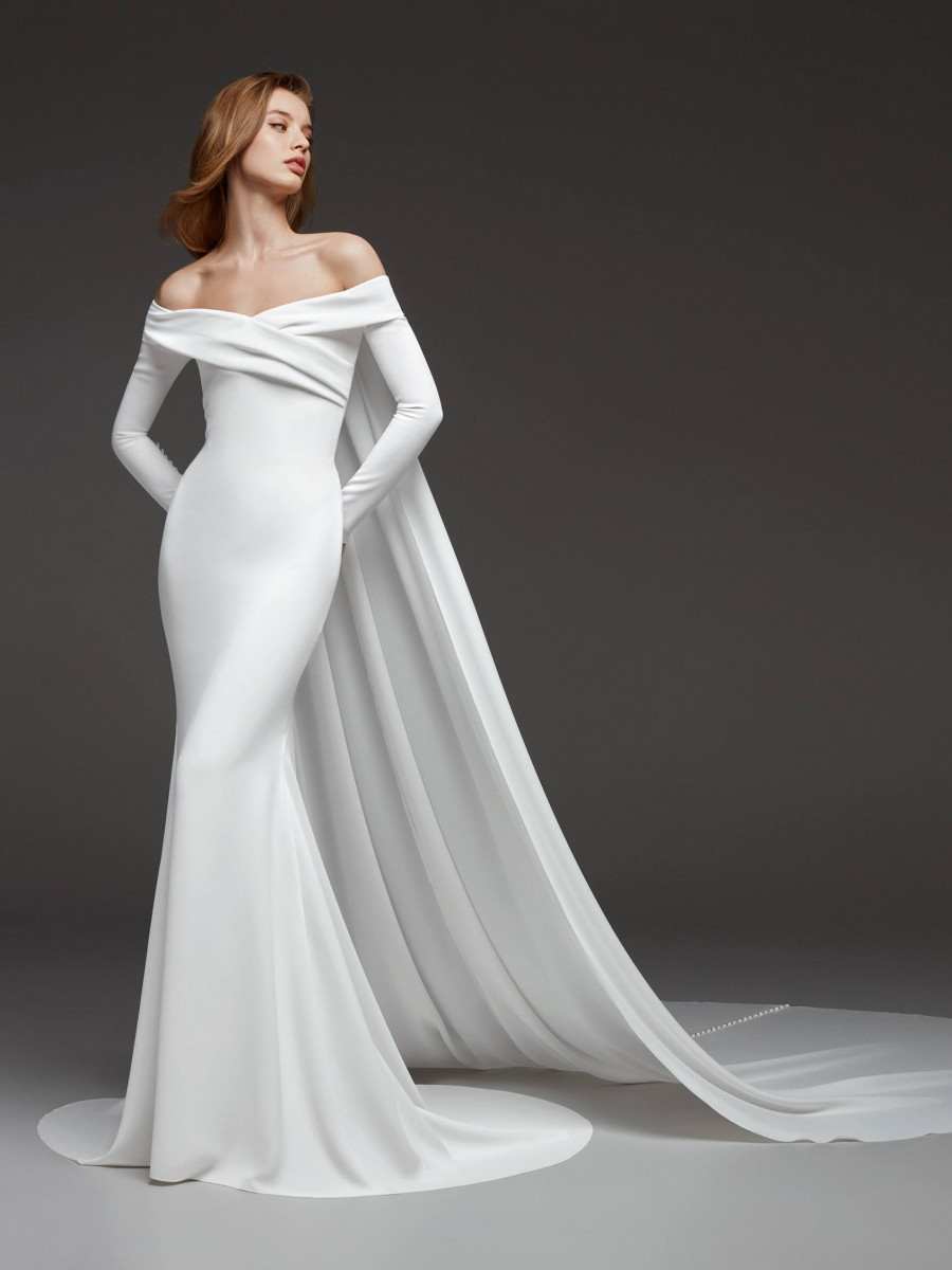 An off the shoulder, sheath wedding dress with long sleeves and a cape