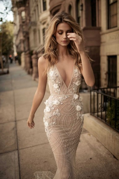 A tight fitting, tan mermaid wedding dress, with low v neckline and beading