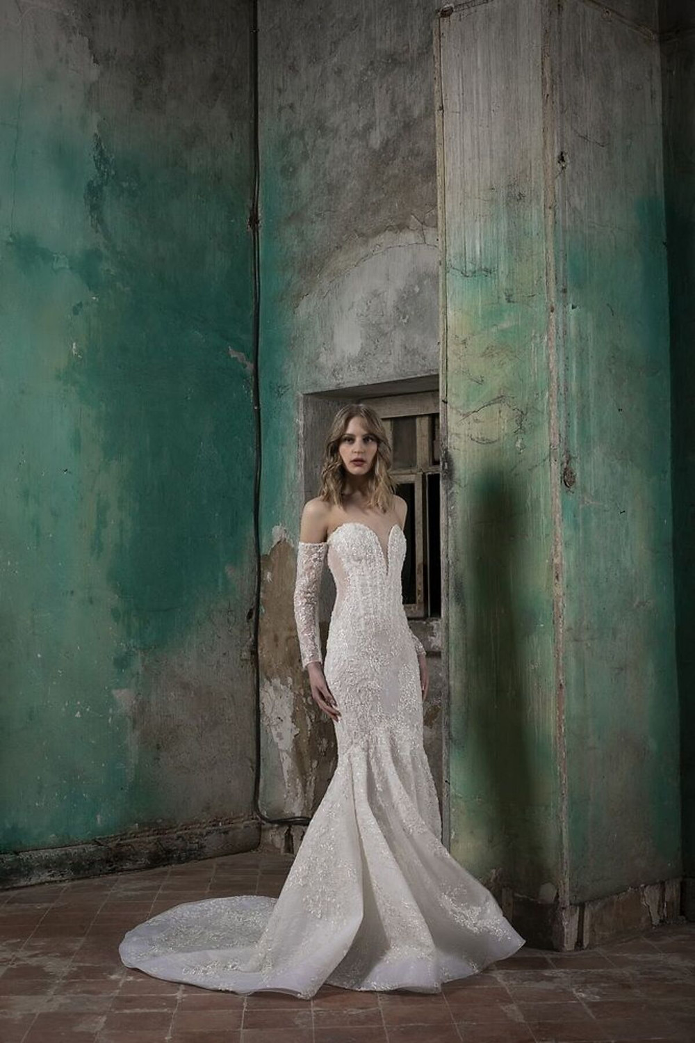 An off-shoulder, long sleeved mermaid wedding gown, intricately embroidered with crystals and featuring a corseted bust