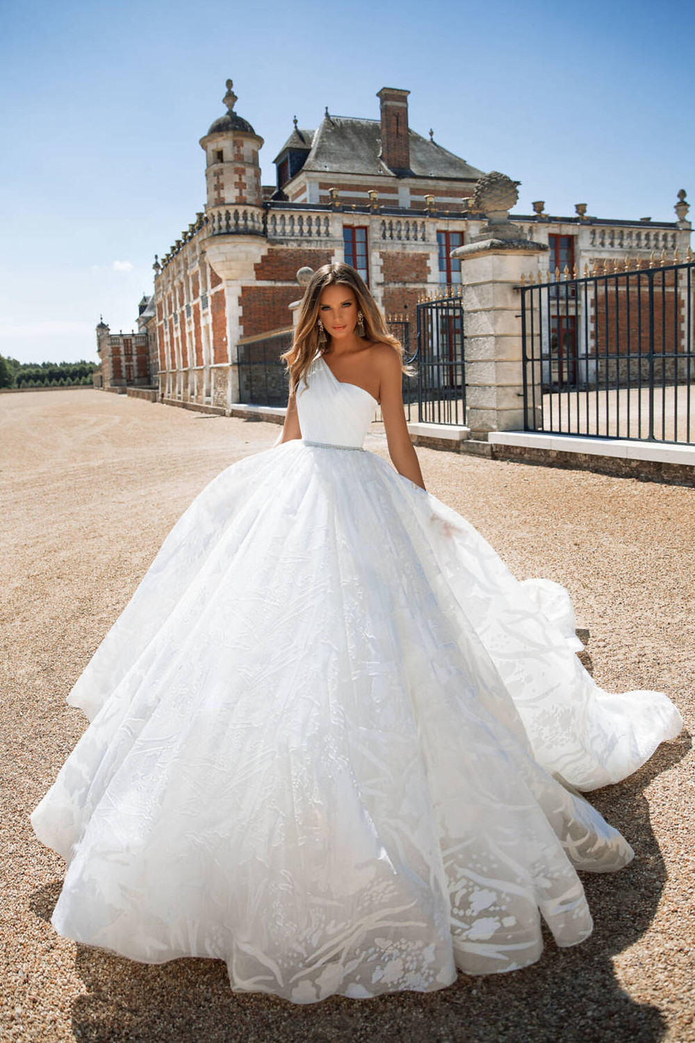 A beautiful one shoulder ball gown wedding dress, with a big skirt and a floral pattern