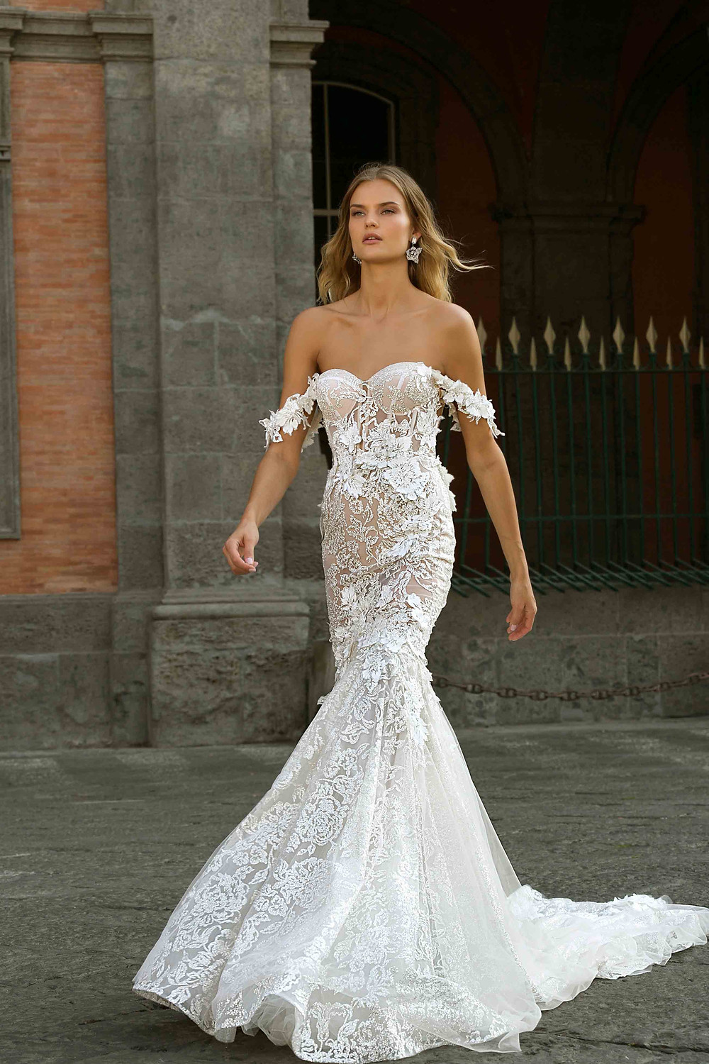 An off the shoulder, corset mermaid wedding dress, with lace and flowers