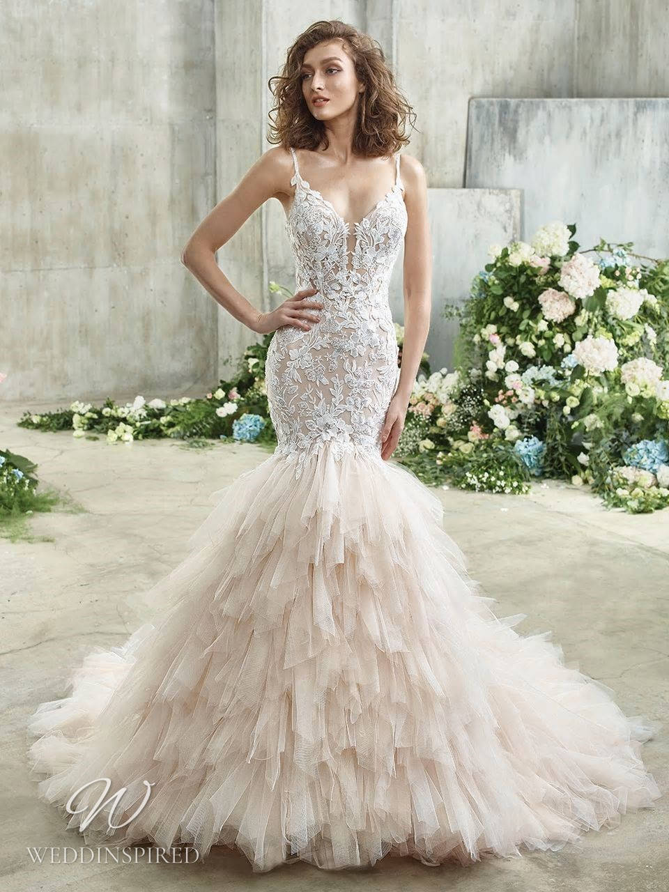 A Badgley Mischka lace mermaid wedding dress with a tulle ruffle skirt and spaghetti straps
