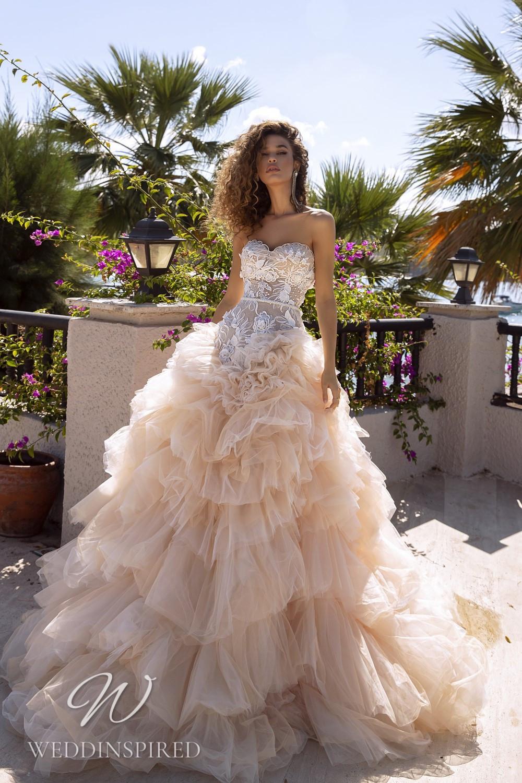 A Tina Valerdi strapless blush tulle princess wedding dress with a ruffle skirt