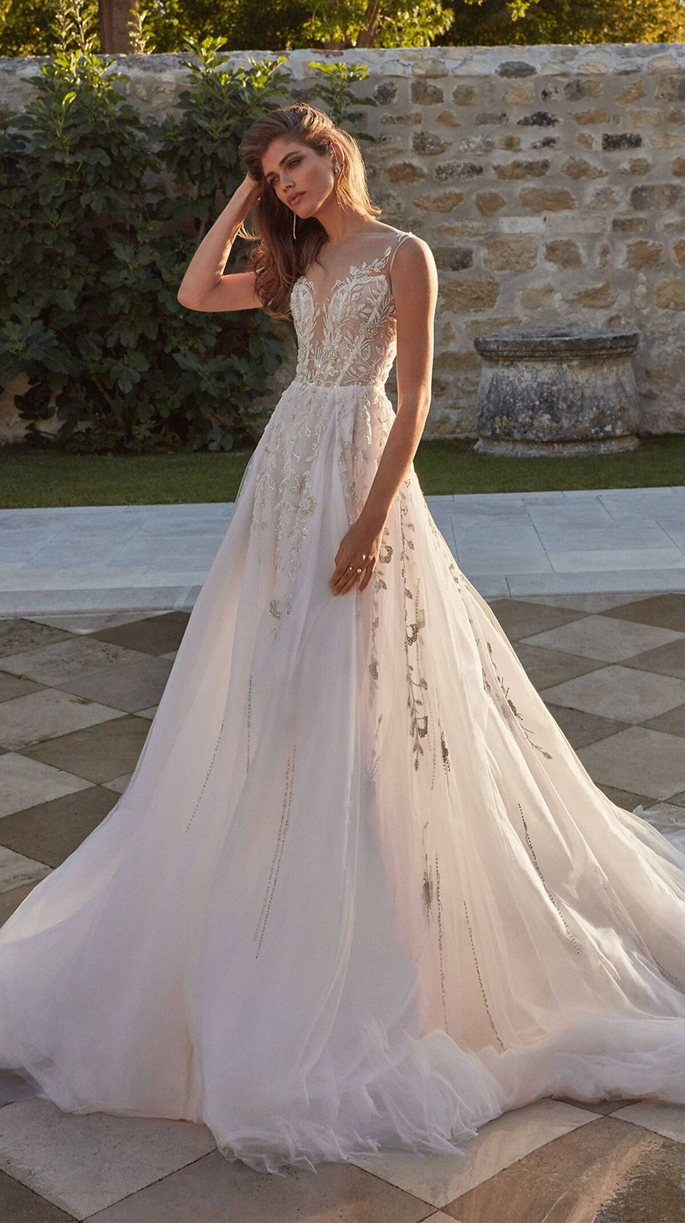 Elaborate embroidery trail down this ice silver and pink A-line ball gown wedding dress with a plunging neckline from the top of the shoulders to the bottom of the full tulle skirt for a one-of-a-kind dress that reflects inner and outer beauty