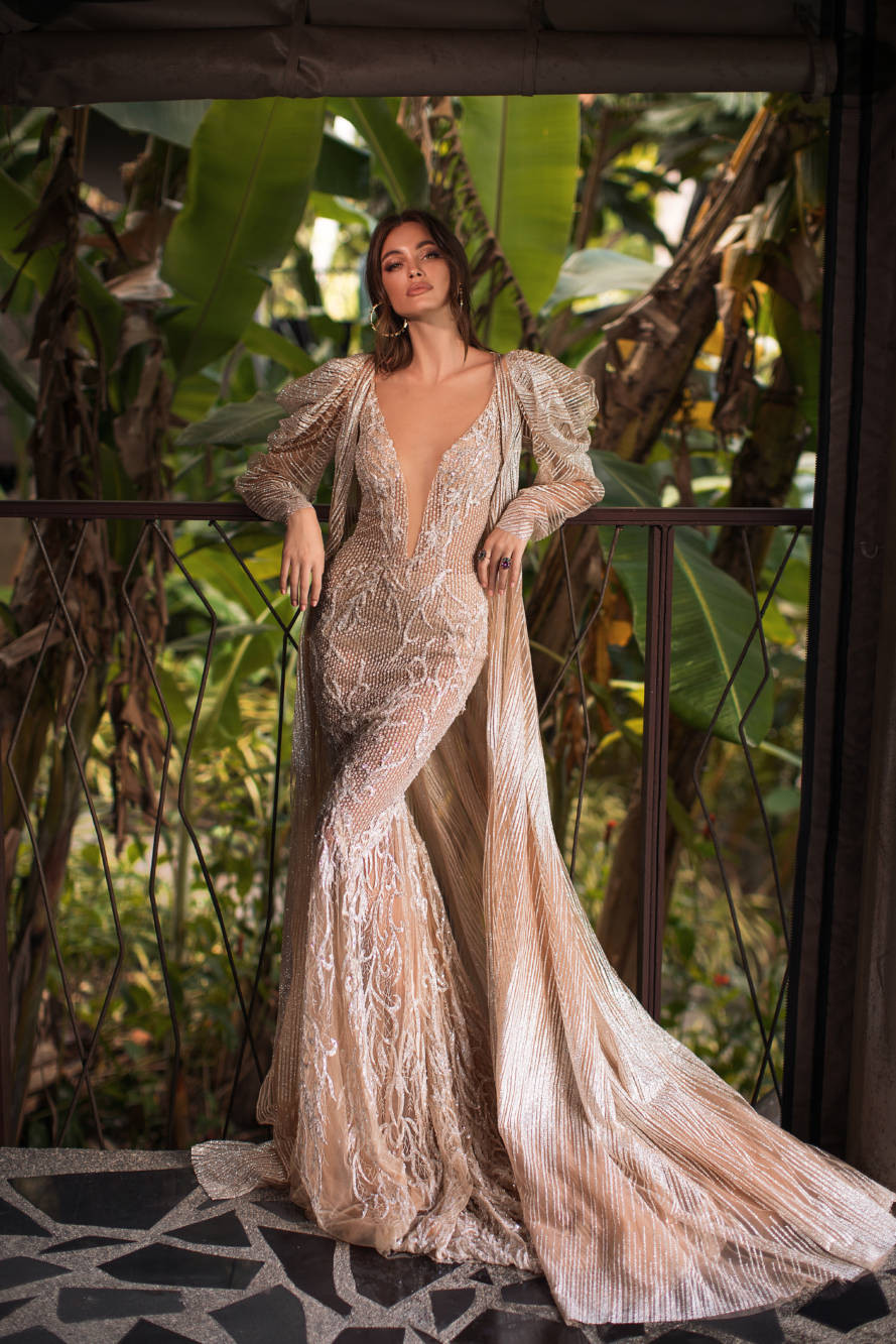 A Milla Nova blush mermaid wedding dress, with stripe pattern, low v neckline, long sleeves and a cape