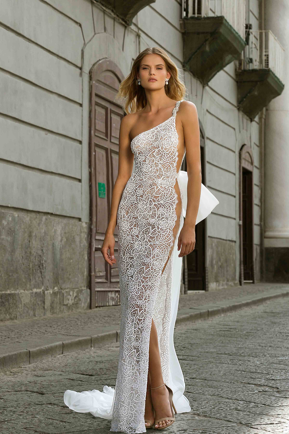 A one shoulder lace sheath wedding dress, with a high slit, a thin strap and a large bow
