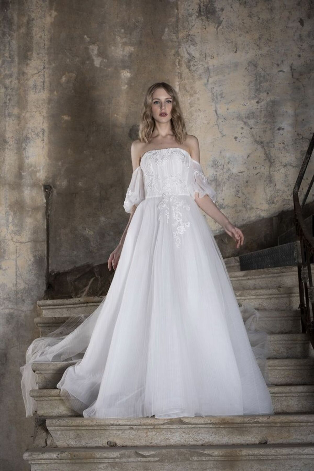 An off-shouldered wedding gown featuring sequined embroideries and a voluminous A-line tulle skirt