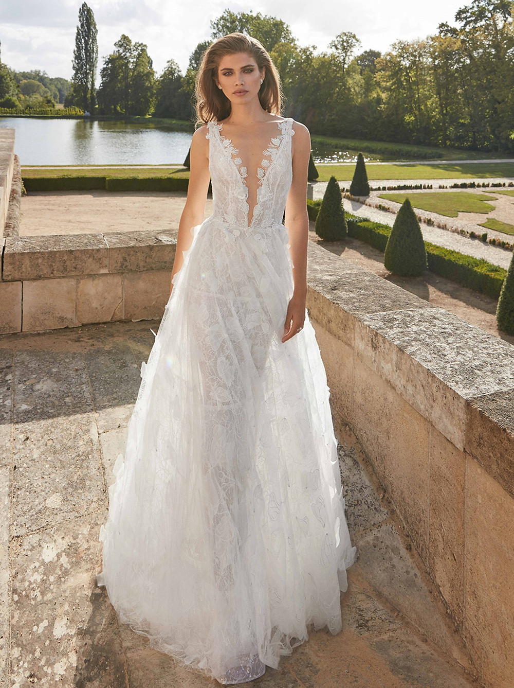 Romantic 3D organza and tulle petals and all-over embroidery bring this multi-layered A-line wedding gown with a plunging neckline to new heights. A sheer, structured petticoat falls from the waist with layers of lace, shimmering tulle, and delicate silk tulle embellishments