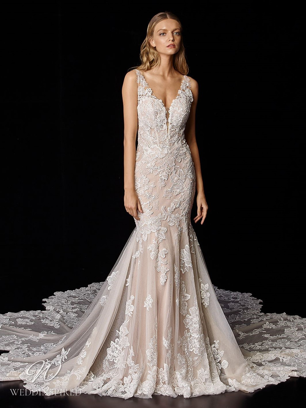 An Enzoani romantic blush lace mermaid wedding dress with a long lace illusion train