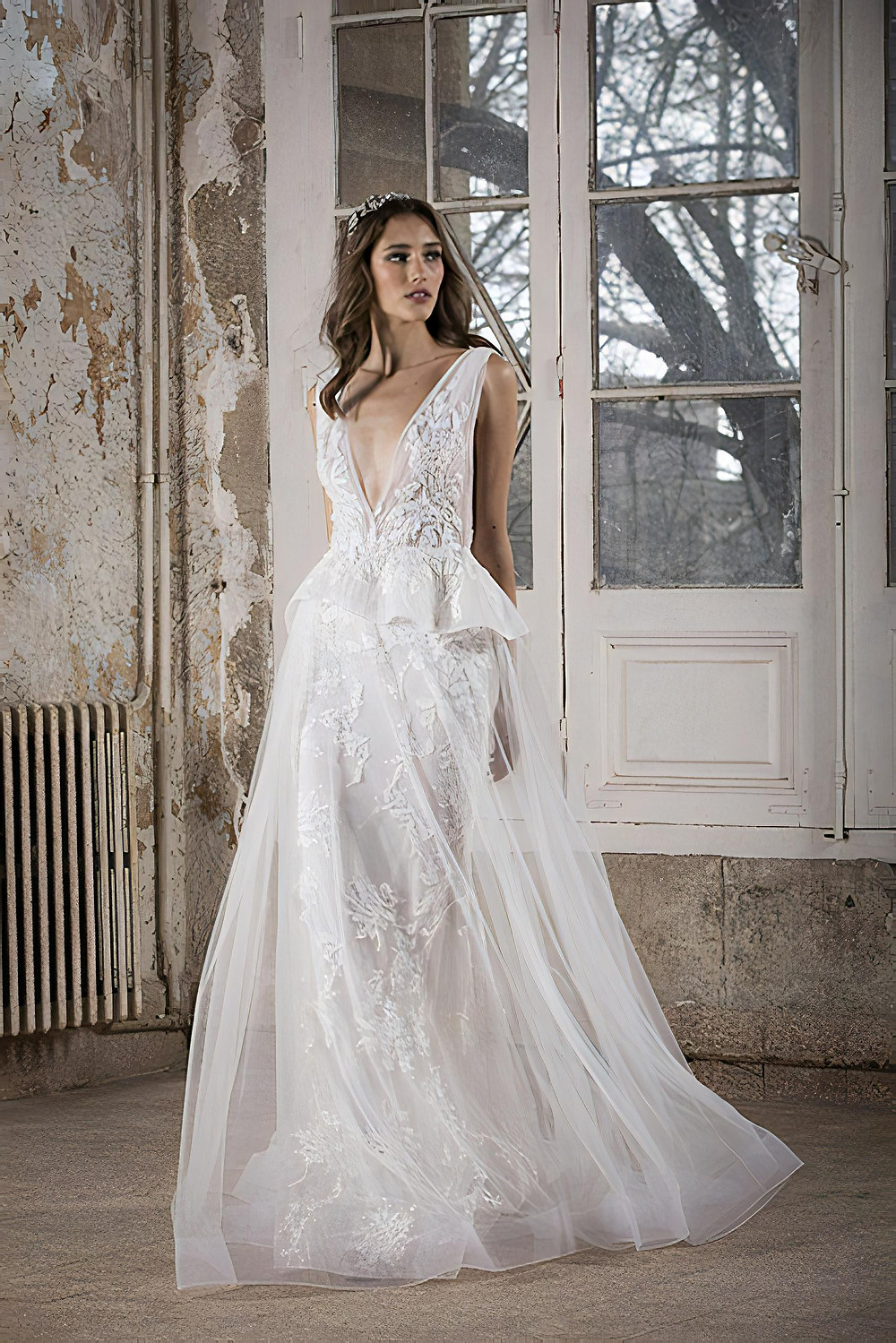 A mermaid cut lace wedding dress featuring a deep-V neckline, with organza peplums and a sheer tulle overlay